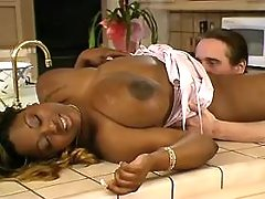 Busty black BBW titfucks in kitchen