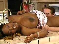 Busty black BBW titfucks in kitchen